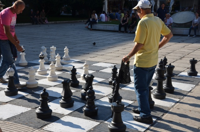 Men playing chess on a giant board