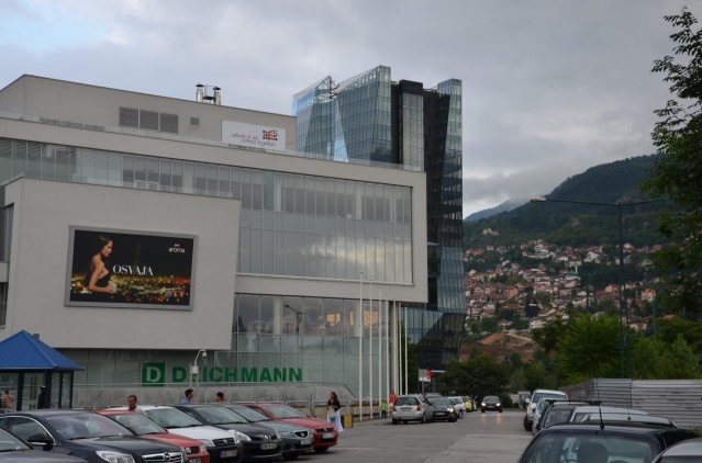 In the foreground, a mega mall, in the background rolling hills at Sarajevo, Bosnia and Herzegovina.