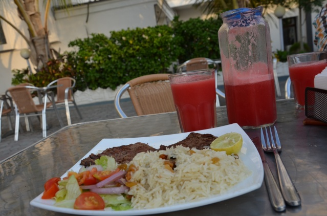 A healthy lunch served at the hotel: Rice with raisins, steak and salad, washed down with fresh melon juice.