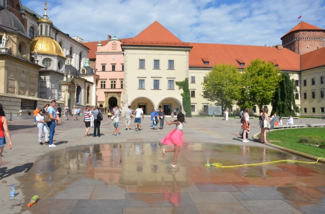 My daughter splashes around in the courtyard of Wawel castle