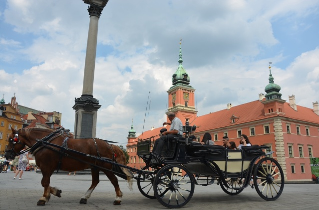 A horse carriage goes by, with the backdrop of the castle
