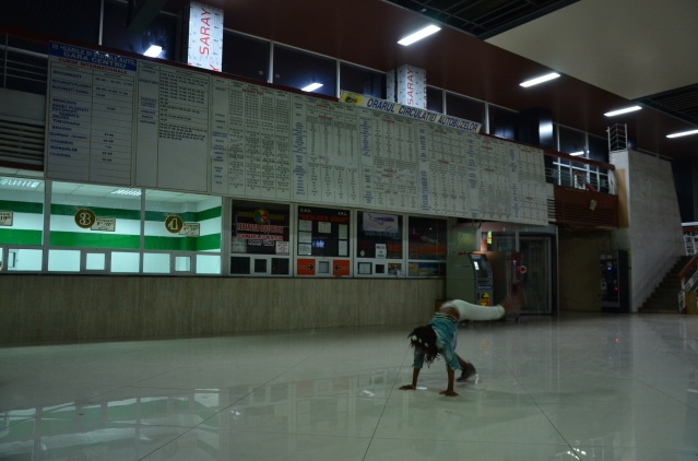 My daughter passes time somersaulting in the bus station.